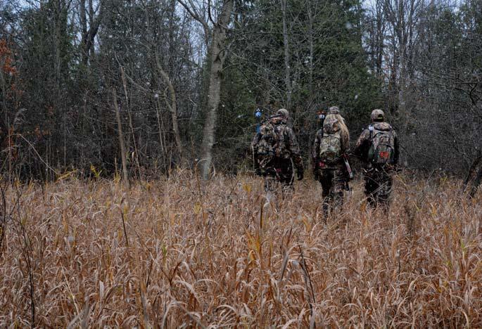 Three hunters walking through field